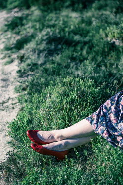 Magdalena Russocka womans feet in red shoes lying on meadow Women