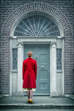 Magdalena Russocka woman in red coat standing at door Women