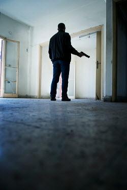 Mohamad Itani MAN HOLDING GUN BY DOORWAY Men