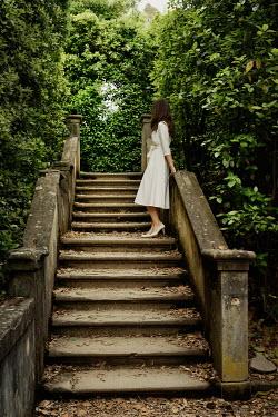 Nikaa WOMAN IN WHITE DRESS ON STONE STEPS Women