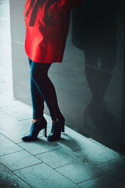 Ildiko Neer woman standing by wall in red coat Women