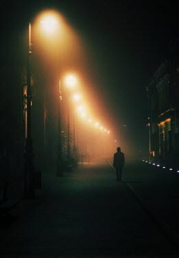 Felicia Simion MAN WALKING IN LIT STREET Men