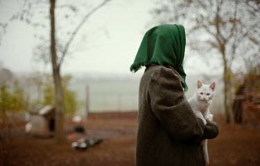 Felicia Simion WOMAN IN HEADSCARF WITH CAT IN COUNTRYSIDE Women