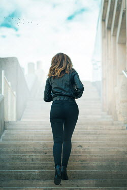 Ildiko Neer Young woman climbing city steps Women