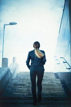 Ildiko Neer modern blonde woman climbing steps Women