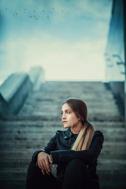 Ildiko Neer Young modern woman sitting on steps Women