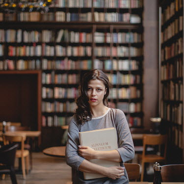 Dasha Pears WOMAN HOLDING BOOK IN LIBRARY Women