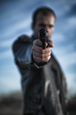 Magdalena Russocka blurred man aiming gun under blue sky Men