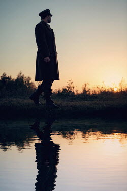 Magdalena Russocka silhouette of soldier reflected in river at sunset Men
