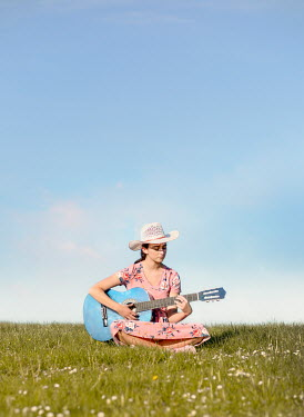 Mary Wethey GIRL PLAYING GUITAR IN SUMMERY FIELD Women