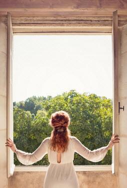Holly Leedham WOMAN INDOORS OPENING WNDOWS IN SUMMER Women