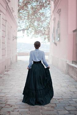 Ildiko Neer Victorian woman standing in cobbled street Women