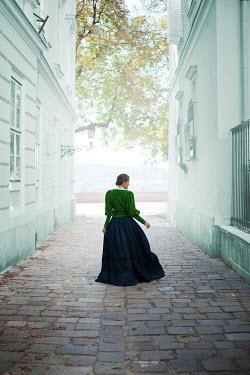Ildiko Neer Historical woman walking in cobbled street Women