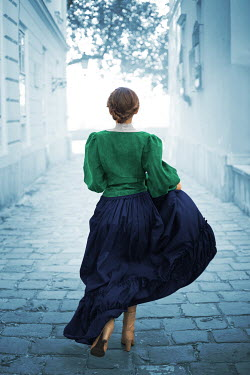 Ildiko Neer Historical woman running in cobbled street Women