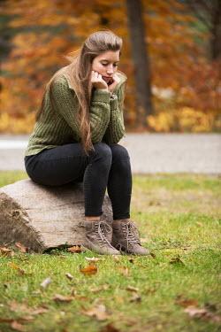 Terry Bidgood TEENAGER SITTING ON ROCK IN PARK Women