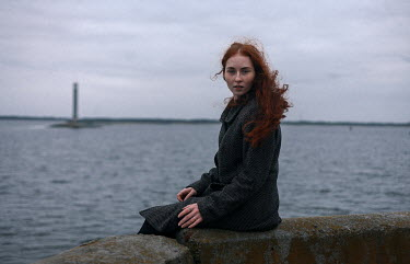 Dmitriy Bilous GIRL WITH RED HAIR SITTING ON SEA WALL Women