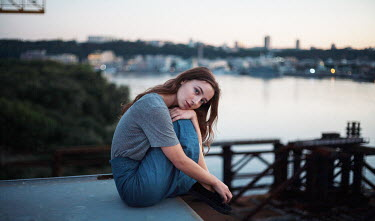 Dmitriy Bilous WOMAN SITTING BY RIVER WITH CITY Women