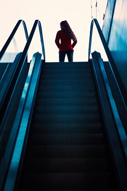 Magdalena Russocka silhouetted girl leaving top of escalator Women