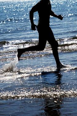 Ute Klaphake SILHOUETTED MAN RUNNING IN SUNLIT WATER Men