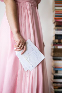 Aida Redzepagic WOMAN IN PINK BY BOOKS HOLDING LETTER Women