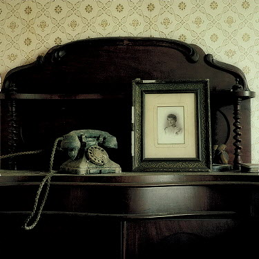 Brian Wells OLD TELEPHONE ON SIDEBOARD WITH PHOTOGRAPH Miscellaneous Objects