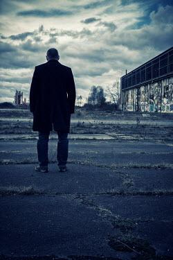 Mohamad Itani MAN IN BLACK COAT IN WINTRY URBAN LANDSCAPE Men