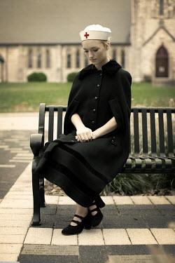 Robin Macmillan YOUNG VINTAGE NURSE SITTING ON BENCH Women