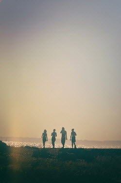 Nicola Smith FOUR PEOPLE WALKING BY SEA IN SUMMER Groups/Crowds
