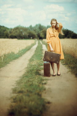 Daniel Bidiuk WOMAN WITH SUITCASES STANDING IN COUNTRYSIDE Women