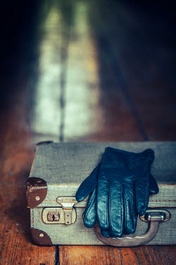 Magdalena Russocka vintage suitcase and gloves on wooden floor Miscellaneous Objects
