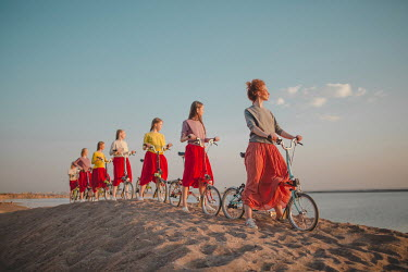 Dasha Pears WOMAN AND GIRLS CYCLING ON SAND DUNE Groups/Crowds