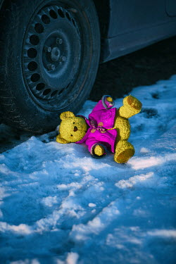 Magdalena Russocka teddy bear lying next to car wheel