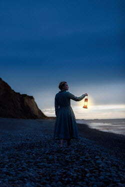 Rekha Garton WOMAN HOLDING LANTERN ON BEACH Women