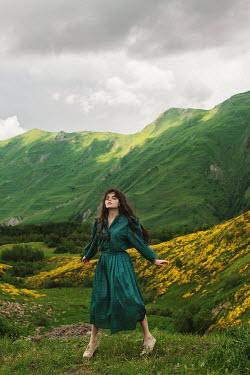 Tatiana Mertsalova BRUNETTE WOMAN STANDING BY GREEN  HILLS Women