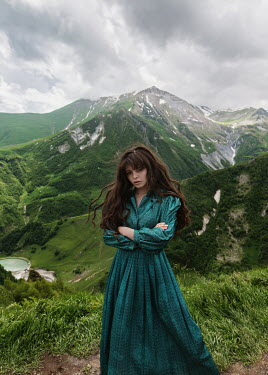 Tatiana Mertsalova SERIOUS BRUNETTE WOMAN ON HILL WITH MOUNTAINS Women
