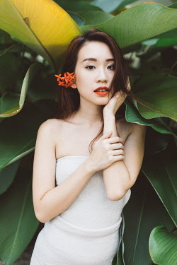 Lalita CLOSE UP OF ASIAN GIRL WITH LARGE PLANT Women