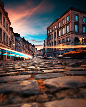 David Keochkerian CAR LIGHTS IN CITY STREET AT DUSK Specific Cities/Towns