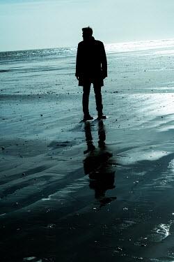 CollaborationJS A silhouette figure walking along the wet sand Men