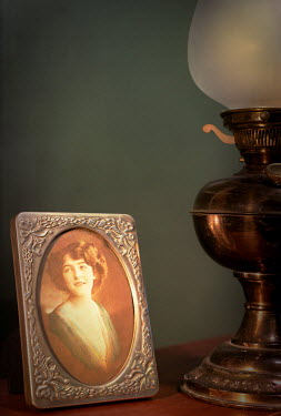 Peter Chadwick OIL LAMP WITH PHOTOGRAPH ON TABLE Women