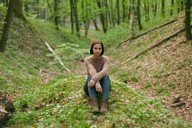 Dmitriy Bilous WOMAN SITTING ON MOUND IN WOODS Women