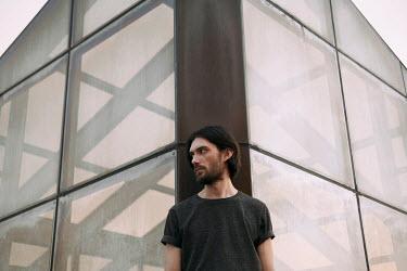 Dmitriy Bilous BEARDED MAN STANDING NEAR GLASS BUILDING Men