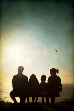 Miguel Sobreira SILHOUETTED FAMILY SITTING BY SEA AT SUNSET Groups/Crowds