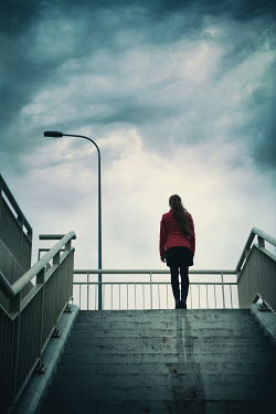 Magdalena Russocka modern woman standing on urban steps under stormy sky Women