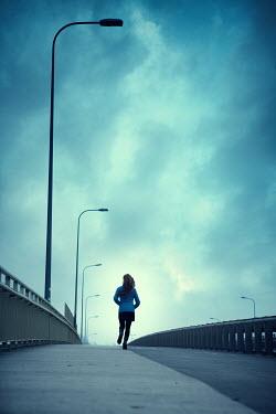 Magdalena Russocka modern woman running on urban footpath Women