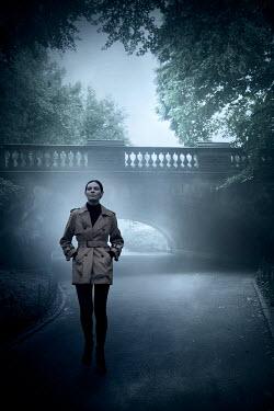 Miguel Sobreira WOMAN IN RAINCOAT WALKING IN PARK Women