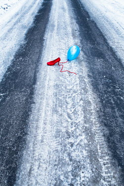 Magdalena Russocka woman's high heel shoe and balloon abandoned on road in winter Women