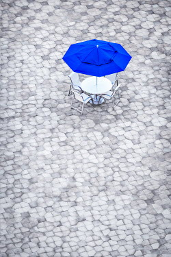 Evelina Kremsdorf TABLE CHAIRS AND UMBRELLA IN EMPTY SQUARE Miscellaneous Objects