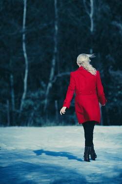 Magdalena Russocka woman wearing red coat walking in snowy field