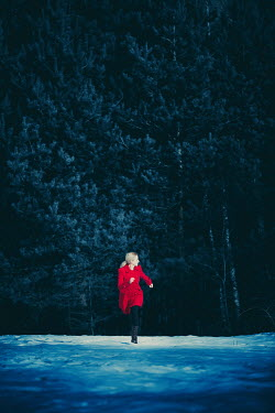 Magdalena Russocka woman wearing red coat running in woods
