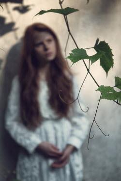 Magdalena Russocka woman standing behind twig of vine.